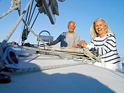 Mature couple on deck of boat, smiling, portrait, low angle view