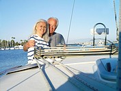 Mature couple arm in arm on deck of boat, smiling, portrait