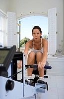 Young woman using exercise machine (thumbnail)