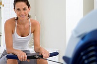 Young woman on exercise machine, smiling, portrait