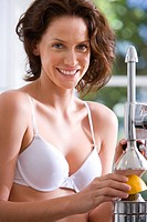 Young woman in underwear with juicer, smiling, portrait, close-up