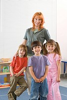 Teacher with students 3-7, smiling, portrait