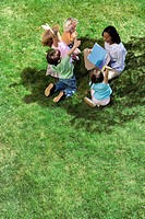 Teacher reading book to children 5-9 outdoors, elevated view (thumbnail)
