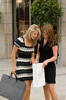 Young women looking in shopping bag (thumbnail)