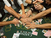 Detail of arms reaching for money at poker game
