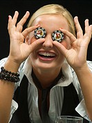 Silly woman holding poker chips over eyes