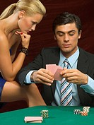 Woman looking at man playing poker