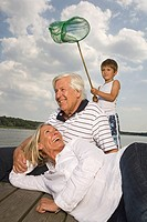 Happy grandparents and grandson near lake