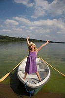 Happy young girl standing in boat with arms lifted