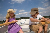 Young boy and girl rowing boat