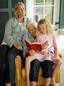 Grandparents reading to granddaughter