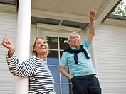 Senior couple waving on veranda (thumbnail)