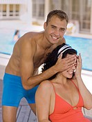 Man covering woman's eyes near pool