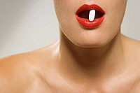 Close-up of a young woman holding a pill in her mouth (thumbnail)