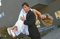Groom throwing bride over his shoulders (thumbnail)