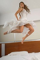 Happy bride jumping on bed