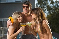 Happy man and women near pool with drinks
