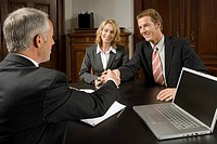 Couple in business meeting and shaking hands with businessman