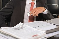 Mid section view of a businessman holding a mobile phone