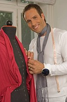 Portrait of a male fashion designer standing beside a mannequin and smiling