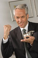Portrait of a businessman holding a bull figurine and clinching his fist