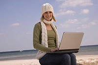 Young woman in winter clothing using laptop at the beach