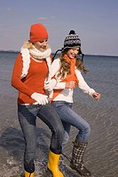 Young women in winter clothing walking in the water at the beach