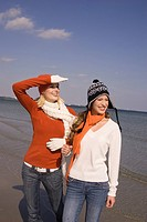 Young women in winter clothing at the beach