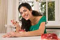 Portrait of a young woman smiling and eating cake at table