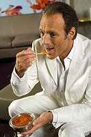 Close-up of a mature man eating caviar with a spoon