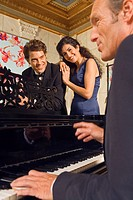 Side profile of a mature man playing a piano with a young couple in front of him (thumbnail)