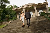 Rear view of a young couple holding each other's hands and moving up on steps