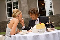 Young man feeding a piece of cake to a young woman