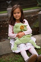 Portrait of a girl holding a stuffed toy (thumbnail)