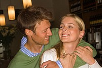 Close-up of a mid adult man embracing a mid adult woman in a bar (thumbnail)