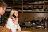 Woman standing at a bar counter and talking on a mobile phone (thumbnail)