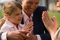 Man and his daughter playing clapping game with woman