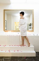 Woman standing next to bubble bath