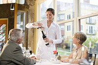 Waitress opening wine for couple