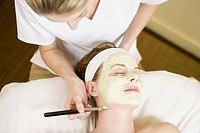 Woman receiving facial spa treatment