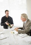 Waiter showing wine bottle to senior man