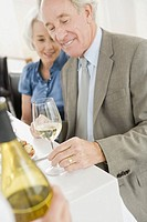 Senior couple looking at wine glass