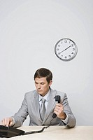 Businessman dialing telephone