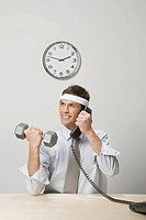Businessman lifting weight while talking on telephone