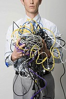 Businessman holding tangle of computer wires