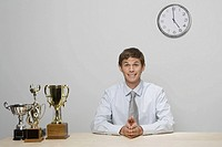 Businessman with trophies on desk