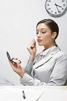Businesswoman applying make up