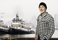 Senior male fisherman in front of fishing boat (thumbnail)