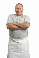 Man wearing apron with arms crossed