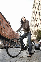 Hispanic woman standing with bicycle